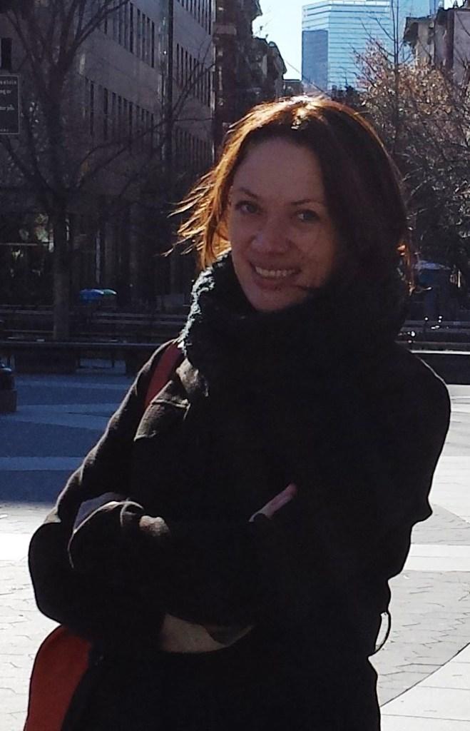 Sissel Undheim smiler mot kamera. Hun står med armene i kryss og har sort jakke og sort skjerf på. Håret hennes er mørkebrunt og ligger som en ramme rundt ansiktet. Hun har en brun veske over skulderen.