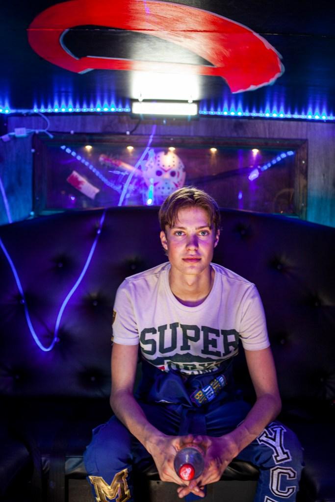 Bussjef Jacob Lyche sit i loungen på bussen. Midtskil, t-skjorte og blå russedress.