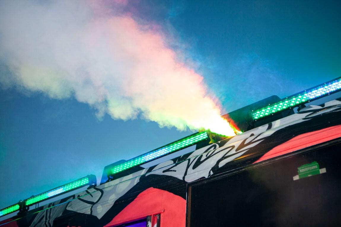 Nærbilete: Røyk og laserlys kjem frå toppen av bussen.