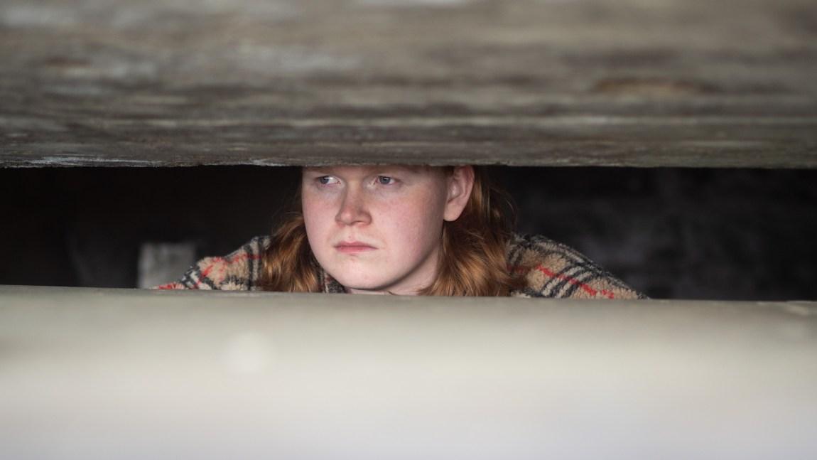 Et bilde av Jon Martin som kikker ut gjennom et hull fra en grotte i Kristiansand