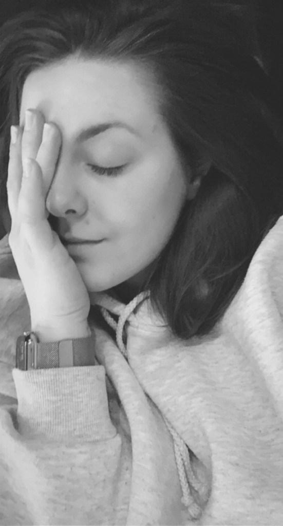 Sort-hvit selfie av Jørunn som ligger med øynene lukket og den ene hånda over høyresida av ansiktet. Hun ser sliten ut, har håret løst ned og en hettegenser på.