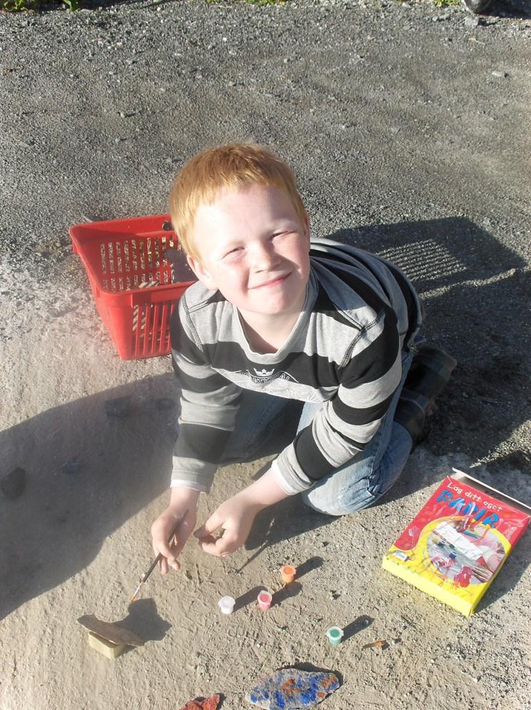 Et bilde av Kill Ginger som barn. Han sitter utendørs og maler steiner i ulike farger.