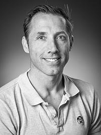 Kirurg Rasmus ser rett inn i kameraet i dette profilbildet som er i sort hvitt. Han har en polotrøye på og han smiler.