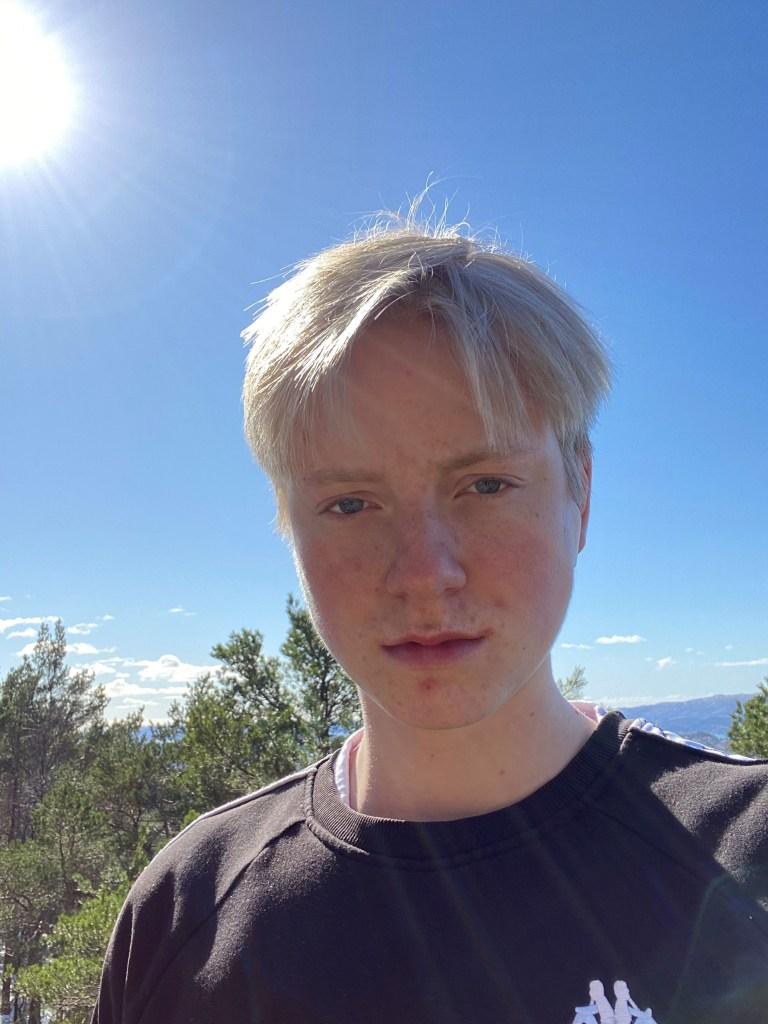 Bilde av Eugene Andersen. Han har en blå himmel bak seg og grønne trær. Det er sol. Eugene har blondt hår og blå øyne. Han er lys. Han har på seg en sort genser med hvit logo.