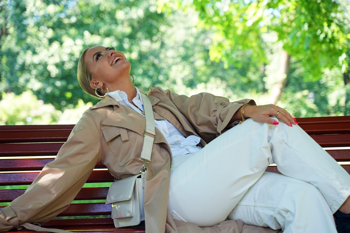 Alexandra sitter på en benk i Frognerparken. Hun løfter beinet opp, ser mot himmelen og ler. Hun har på seg en hvit skjorte og en beige kåpe med en hvit veske hengende over skulderen. Håret et satt opp i en hestehale.