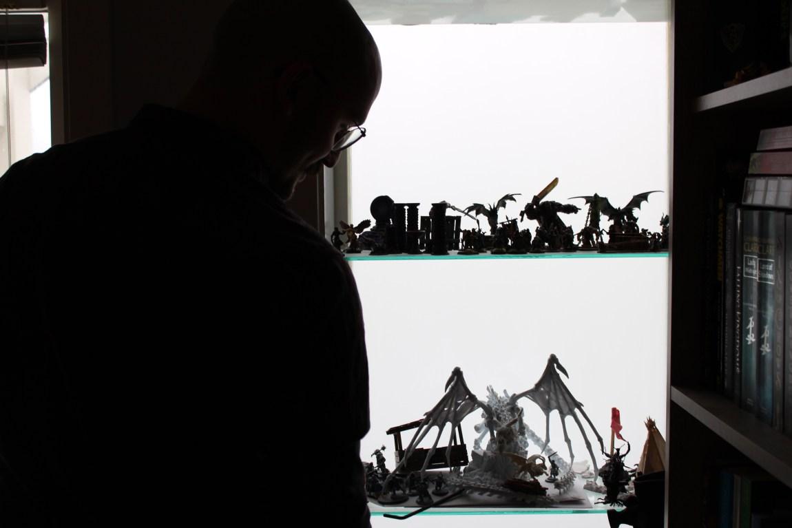Ein ser skyggane av ein mann med briller, og ved han står det to hyller fylt med miniatyrfigurar.