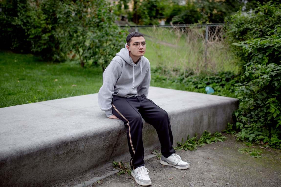 Mert sitter på hendene sine, oppå et stenplatå. Han har på seg briller og en grå hettegenser.