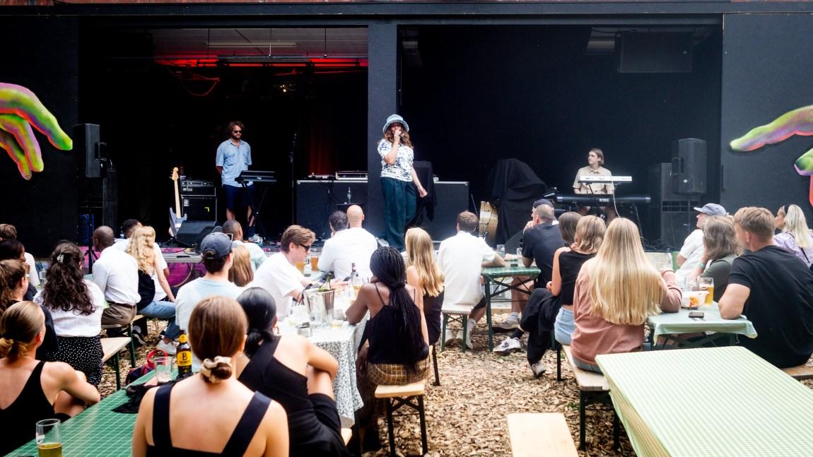 Nedja og to bandmedlemmer på en liten svart scene. Publikum sittende ved piknikbord i forgrunnen.