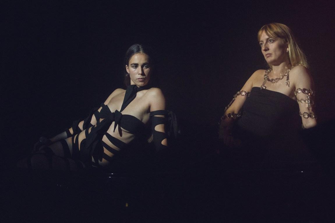 Et bilde av Catharina Stoltenberg og Henriette Motzfeldt i Smerz. De er kledd i sort.