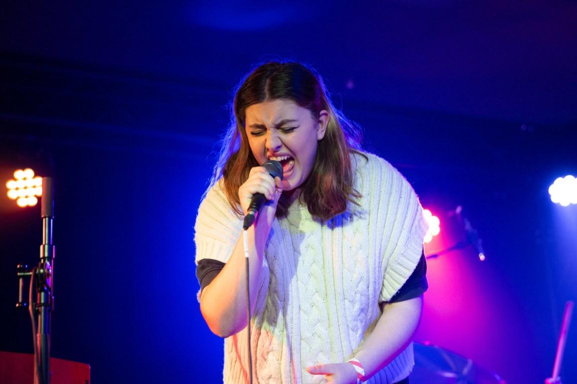 Et bilde av en jente i hvit genser som skriker inn i mikrofonen