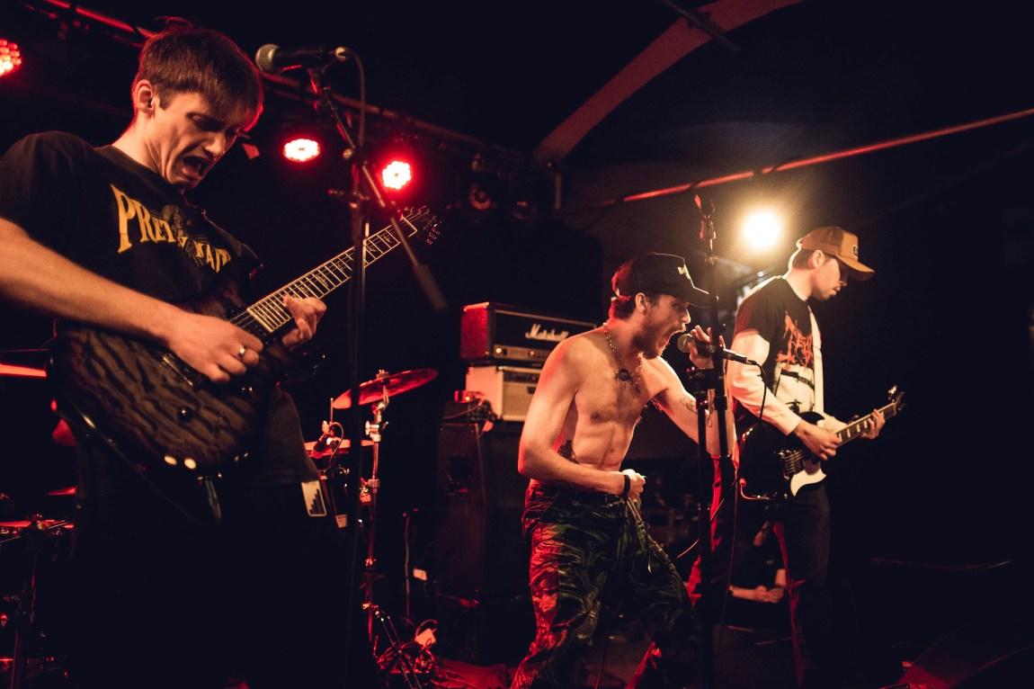 Et bilde av et rockeband. Gitarist og bassist ser nedover, mens vokalist står i baris og skriker inn i mikrofonen mens han ser rett frem
