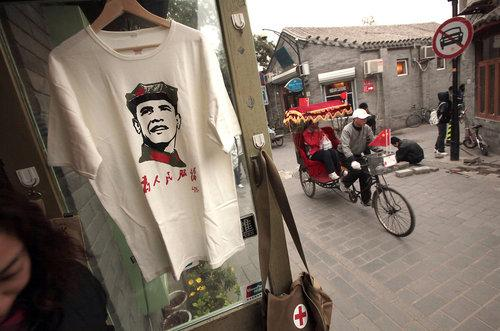 Beijing residents pedal their bikes past an Obama Mao t-shirt for sale.