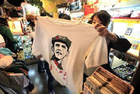 A Chinese woman holds an Obama Mao t-shirt for sale. (From CCTV)