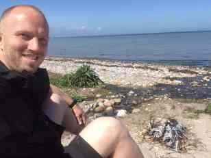 El albino viser sine ben frem og hygger sig lidt med sit bål.