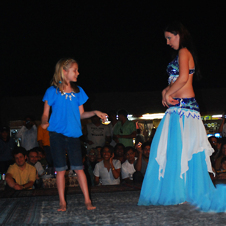 a kid having fun with a belly dancer
