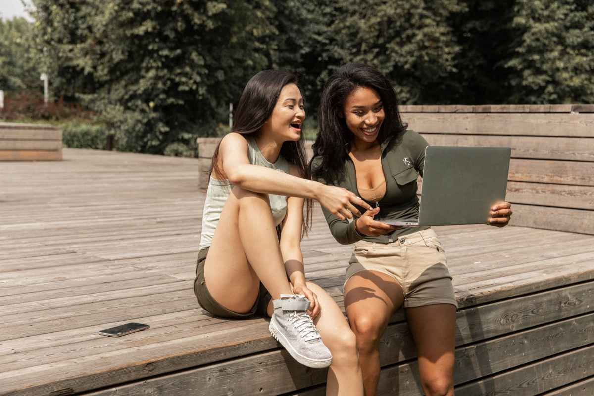 cheerful young multiethnic women sharing laptop and laughing in park