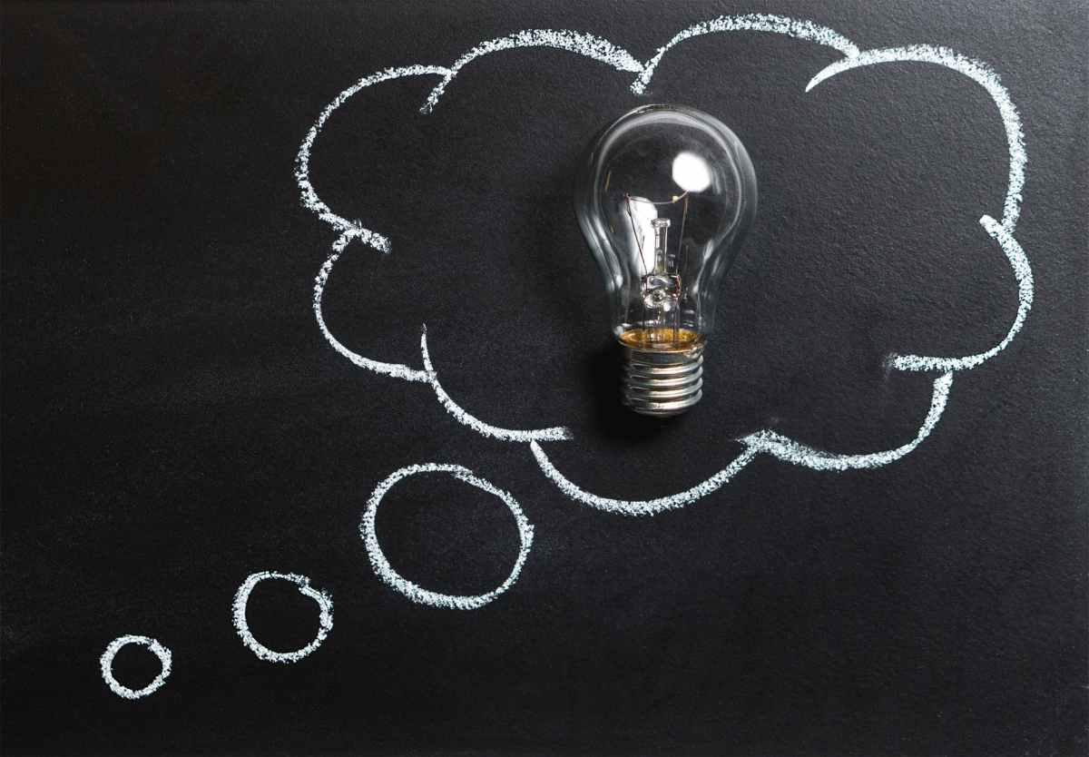 clear light bulb placed on chalkboard