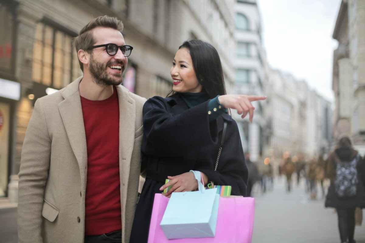 joyful multiethnic adult couple with shopping bags walking along street in downtown