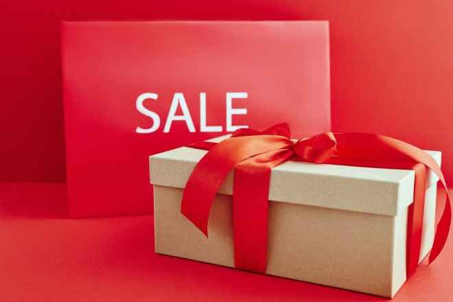 cardboard box with red ribbon beside a sale sign