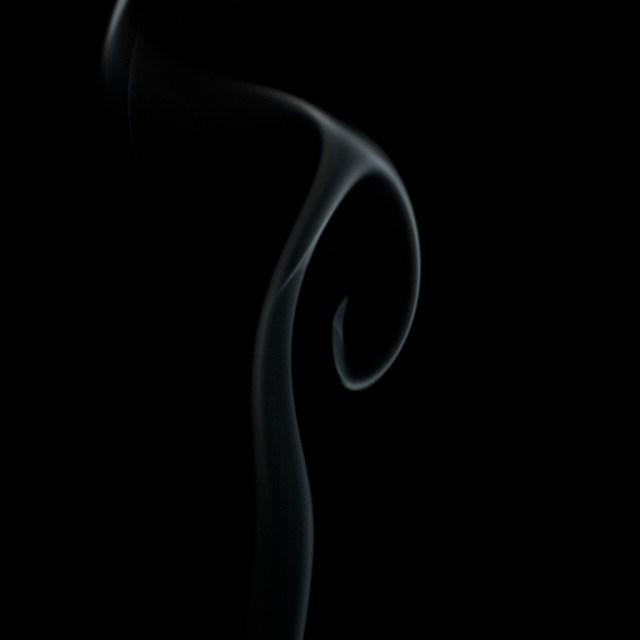 Voluta de humo de incienso retroiluminada sobre fondo negro