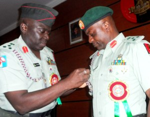 PUBLIC RELATIONS, BRIG.-GEN. IBRAHIM ATTAHIRU (L), DECORATING   HIS SUCCESSOR, BRIG.-GEN. OLAJIDE LALEYE, WITH THE BADGE OF THE DIRECTORATE DURING THE HAND-OVER   CEREMONY IN ABUJA ON TUESDAY (7/1/14). 127/7/1/2014/COA/NAN
