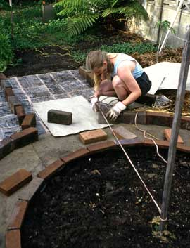 Using a stringline to measure the placement of recycled bricks to edge the garden path around a circular bed. Fiona's bckground in the design professions taught her the importance of accuracy in making durable gardens.