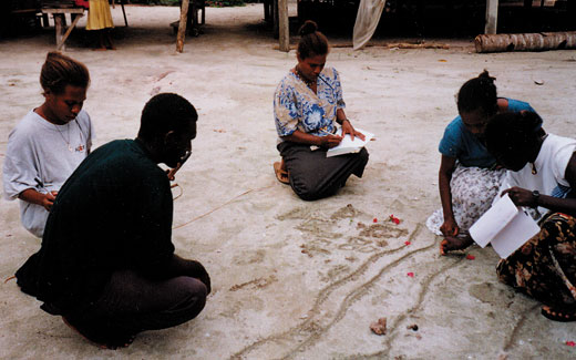 Development workers make an impromptu map in the sand to make decisions about training at Mana'abu village, Manu Lagoon, Malaita island, Solomon Islands. Kastom Gaden Association, TerraCircle projects.