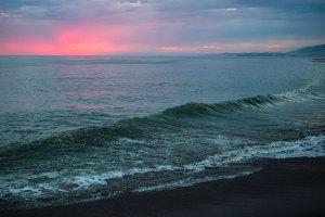 California coastline at dusk with wave crashing