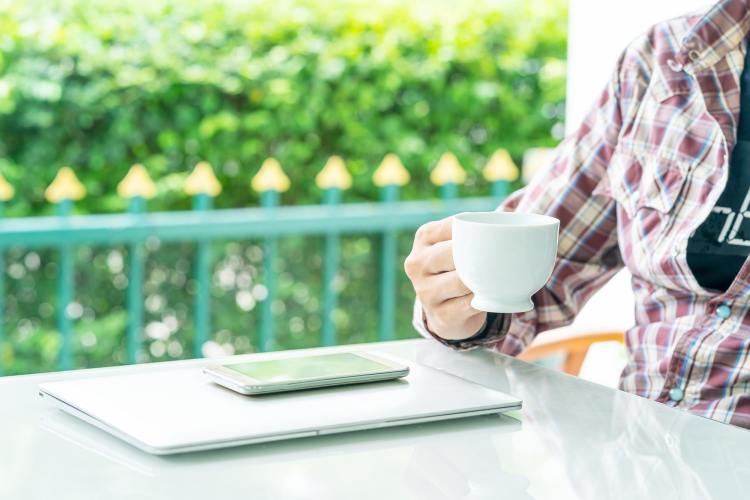 Male hand holding smart phone and cup of coffee_