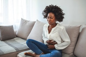 Woman lying on her sofa alone and suffering from period cramps at home