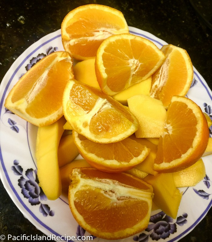 Pealed sliced mango and sliced oranges gives for a good snack.
