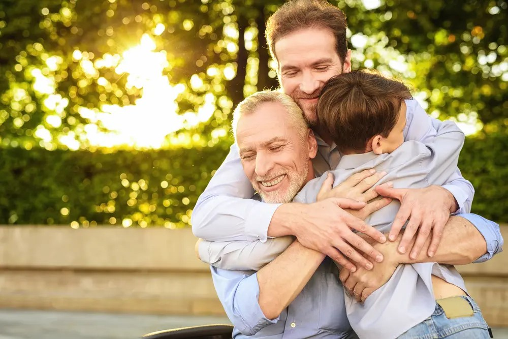 older man with family hugging