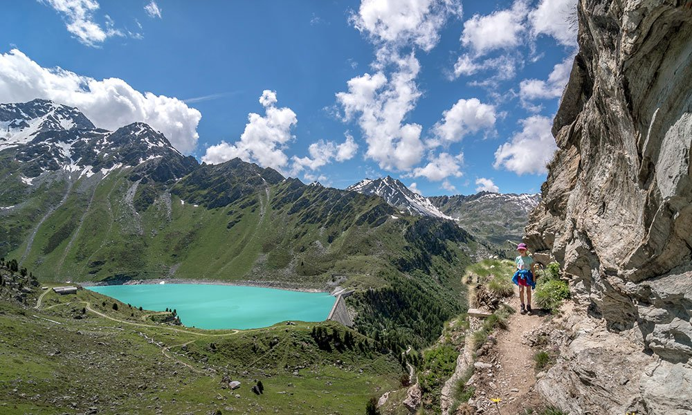 girl hiking along bisse de cherve with mountain lake