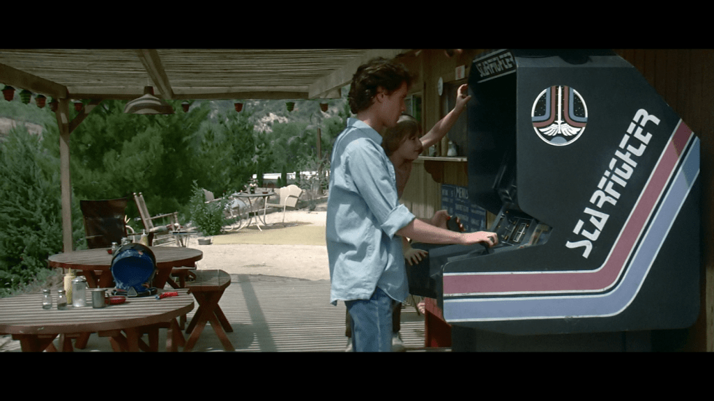 A set of kids playing the game Starfighter in a desert trailer park from the movie The Last Starfighter.