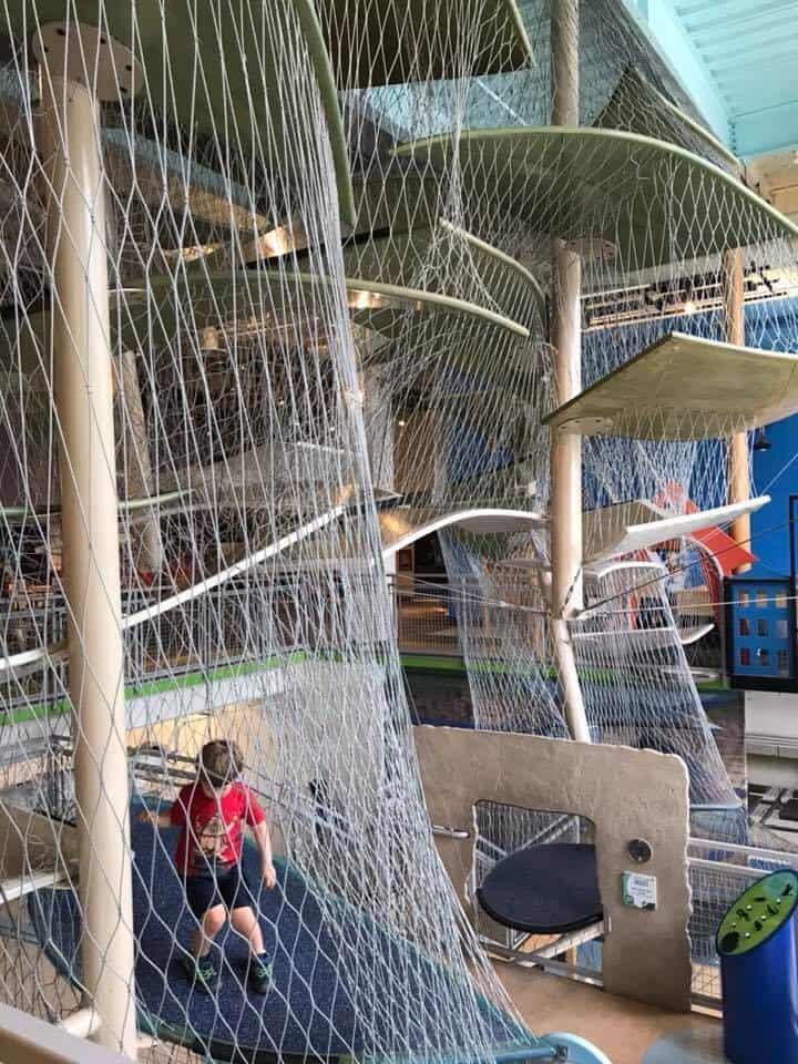 Boy climbing in the net climbing zone at the Glazer Children's Museum