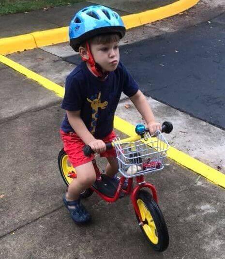 Little boy learning to ride a balance bike.