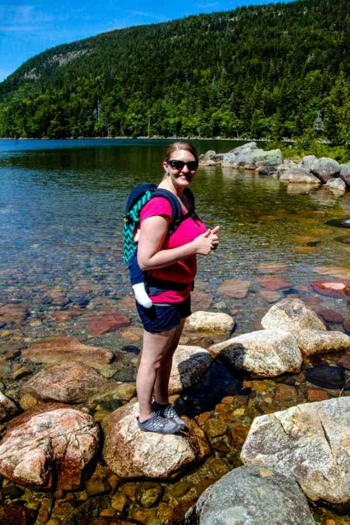 Mom with child in a carrier on her back in front of Jordan Pond in Acadia National Park in Maine