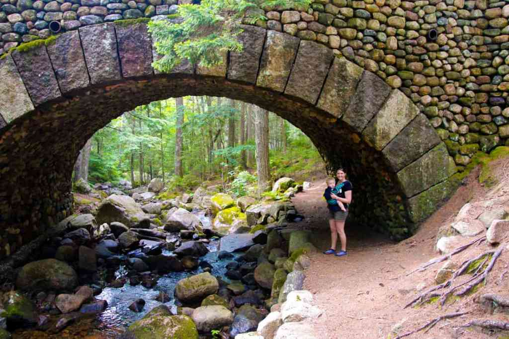 Mom with baby by a bridge off the carriage roads in Acadia National Park in Maine