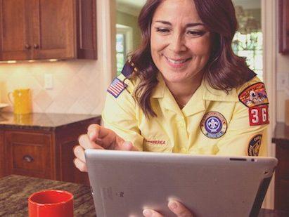 Smiling female leader in yellow uniform shirt taking online training