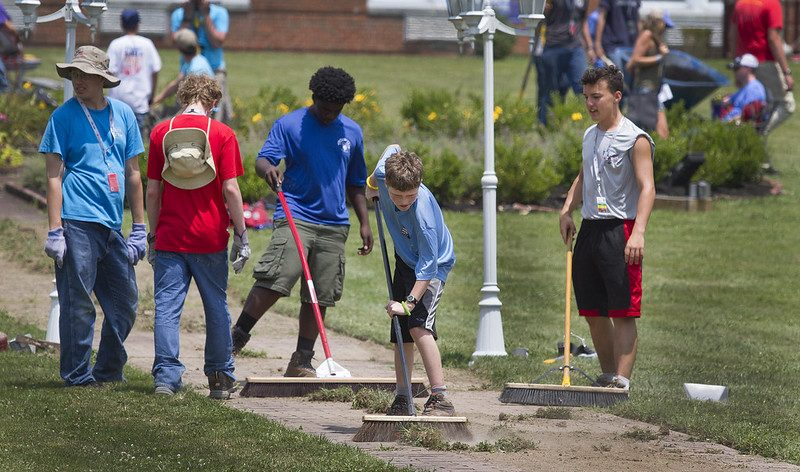Scouting sweeping up grass for service project