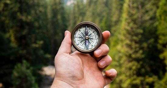 Hand holding compass by mountains