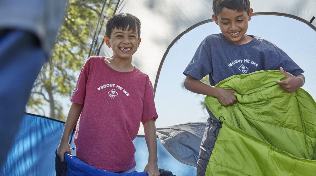 Two happy Cub Scout boys in tent holding sleeping bags