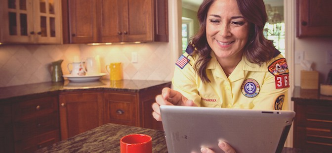 Smiling female leader in yellow uniform shirt taking online training