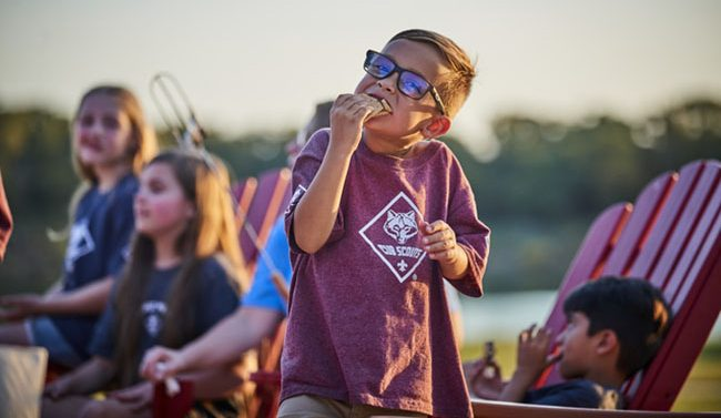 Cub Scout boy eating s'more, girls and lake in background