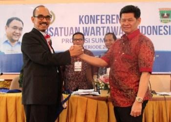 Heranof Firdaus (kiri) bersalaman dengan Ketua PWI Sumbar periode sebelumnya, Basril Basar. (ers)