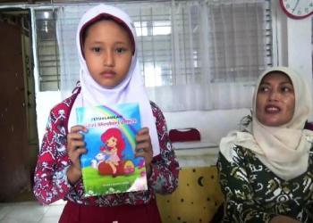 Syadza Hanifa Putri ditemani Wakil Kepala SDN 01 Sawahan Eliwati menunjukkan buku karangannya. (dio)