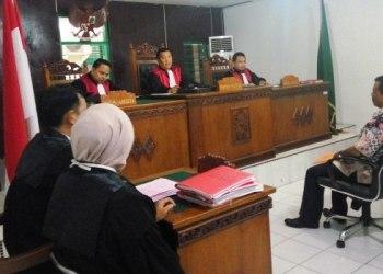 Oknum anggota DPRD Kabupaten Pesisir Selatan Asril Datuak Putiah, terdakwa kasus penganiayaan Walinagari menjalani sidang perdana di PN Painan, Rabu (22/2). (fahmi)
