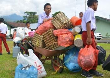 Dua pelajar membawa gerobak sampah untuk ditukarkan dengan sembako. (humas)