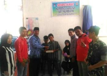 Kepala Perpusda Sumbar menyerahkan buku di kampung literasi dihadiri anggota DPRD Kota Padang, Aprianto. (baim)