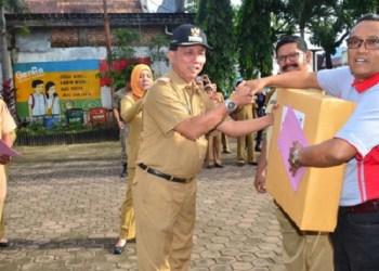 Camat Padang Barat Arfian menyerahkan hadiah kepada kelurahan yang swadayanya tertinggi. (ist)